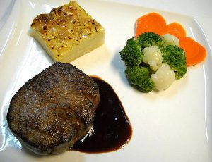Filet Steak `Vienna Dreams` Flamed beef tenderloin in a burgundy sauce, with potato au gratin and vegetables